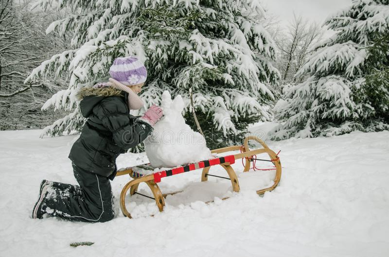 Child having happy winter time with lot of snow and little snowman built in sleight royalty free stock photos