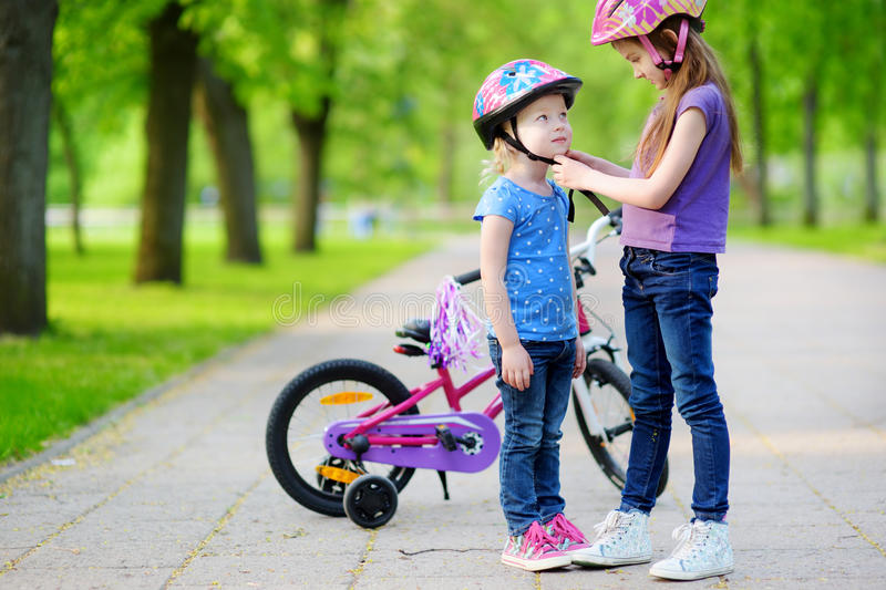 Adorable girl helping her sister to put a bicycle helmet on. Adorable girl helping her little sister to put a bicycle helmet on stock photos