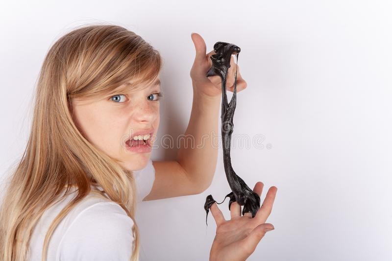 Adorable girl holding a black slime and making royalty free stock photography