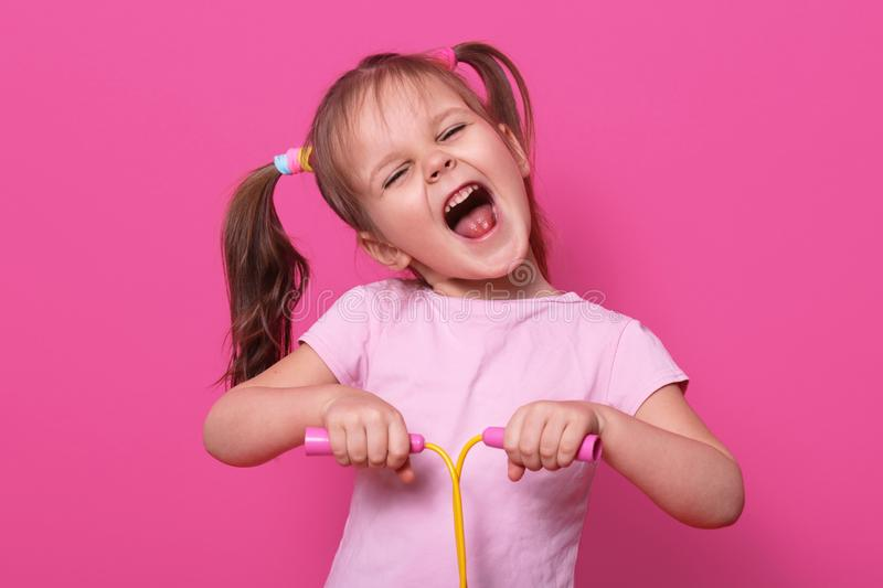 Adorable girl holds skipping rope in hands. Charmig female child with opened mouth and narrowed eyes with happy expression. LIttle royalty free stock photos