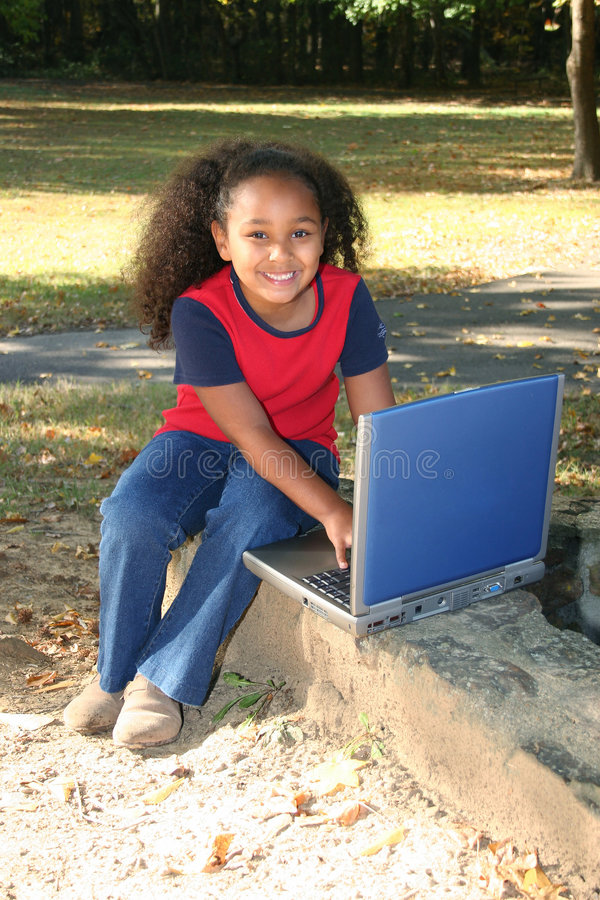 Adorable girl with laptop. Adorable African American girl typing on laptop computer royalty free stock images