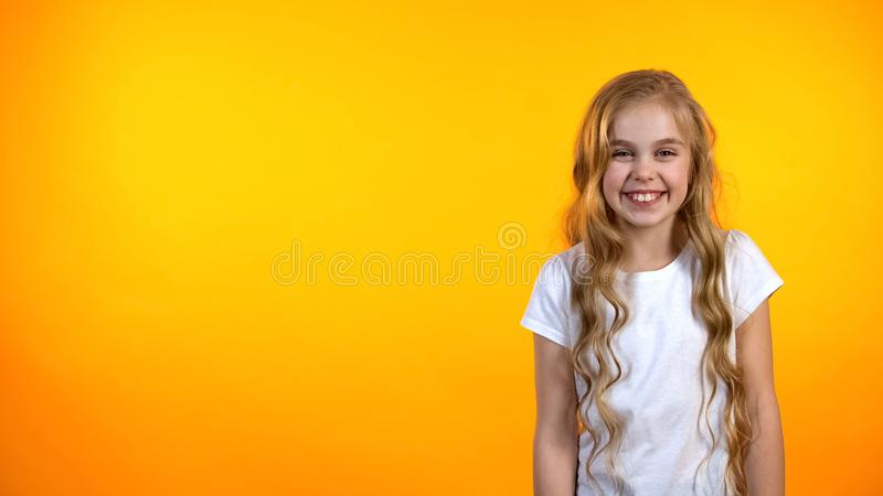 Adorable girl laughing happily standing on orange background, humor and jokes. Stock photo stock images