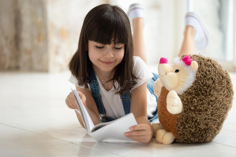 Adorable girl laying on warm floor with favorite toy, reading. Happy smiling adorable school girl laying on warm heated wooden floor with favorite toy, holding royalty free stock photography