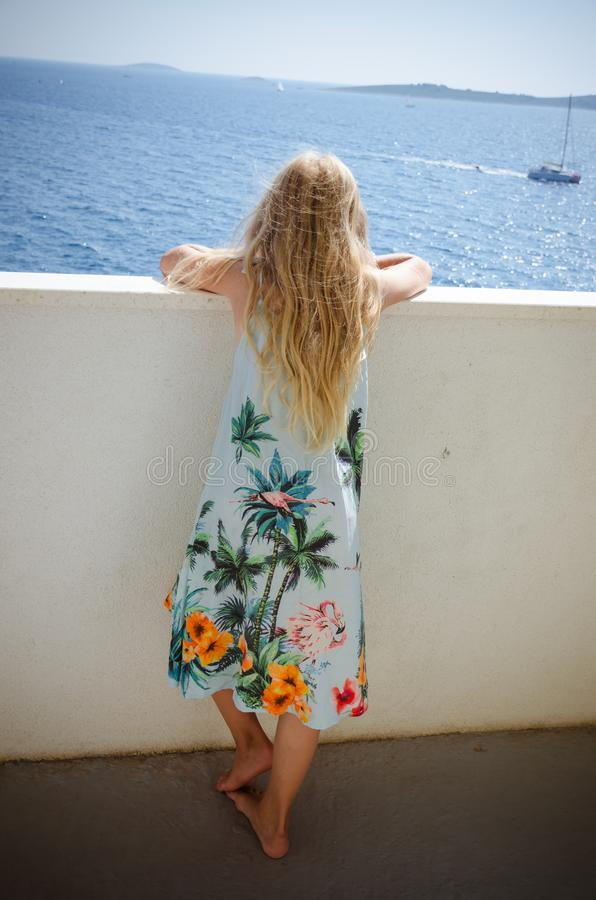 Adorable girl  with long blond hair and summer dress looking from the balcony stock photos