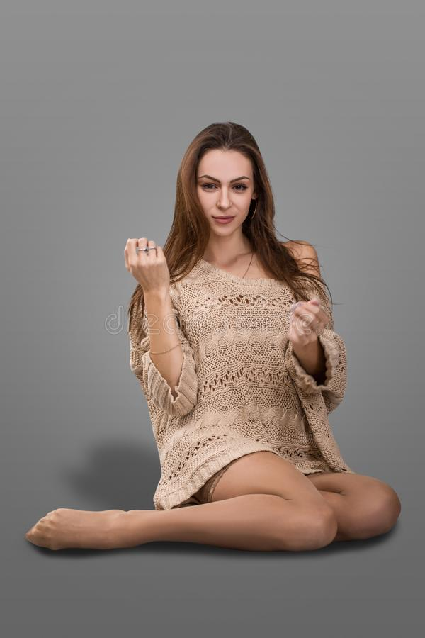 Adorable girl with long hair in a sweater and stockings sitting barefoot on the floor royalty free stock photos