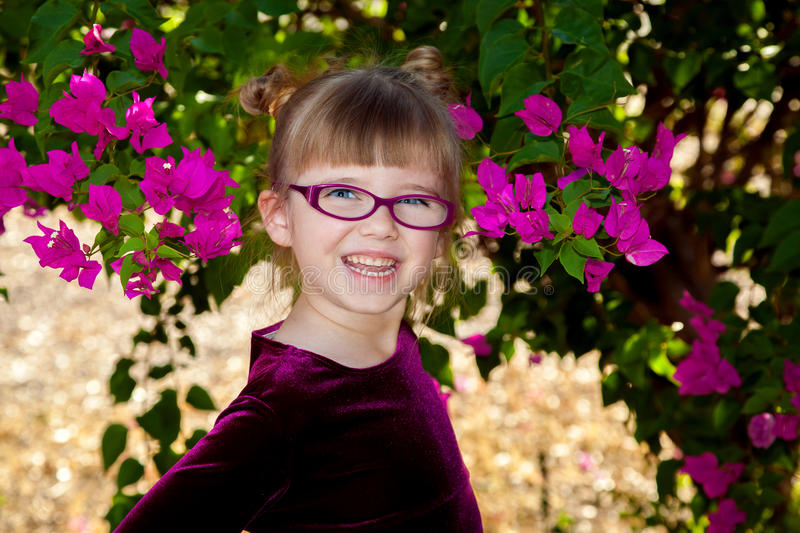 Adorable Girl With Maroon Glasses and Dress Smiling Big. An adorable, young girl with glasses and big, blue eyes, smiles with an open mouth for a portrait. She royalty free stock photo