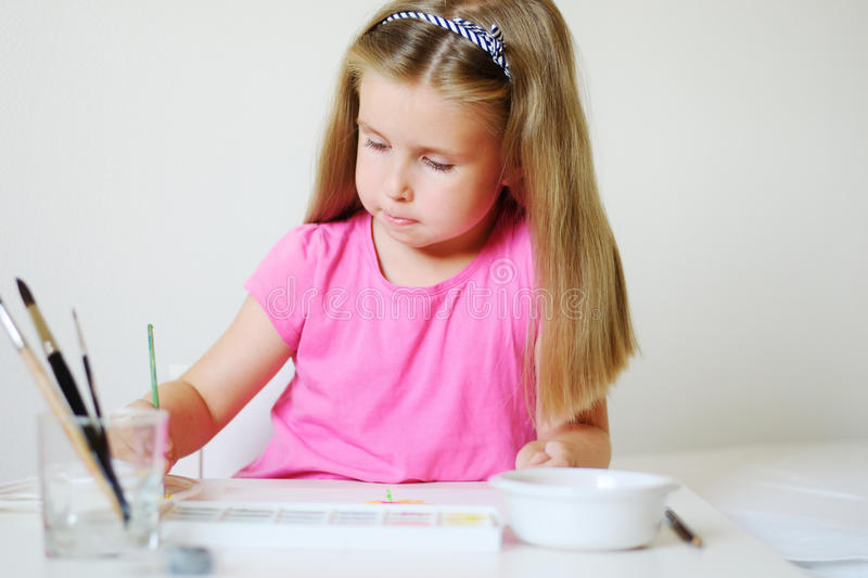 Adorable girl painting with watercolor in a sunny white room at home stock photo
