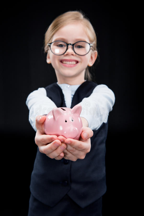 Adorable girl with piggy bank stock images