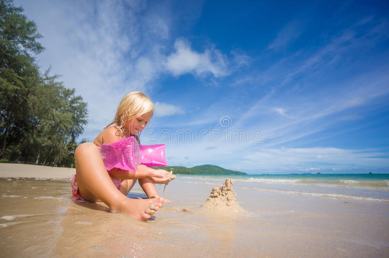 Adorable girl in pink swimming suit and inflatable arm bands build sand tower on ocean beach stock photography