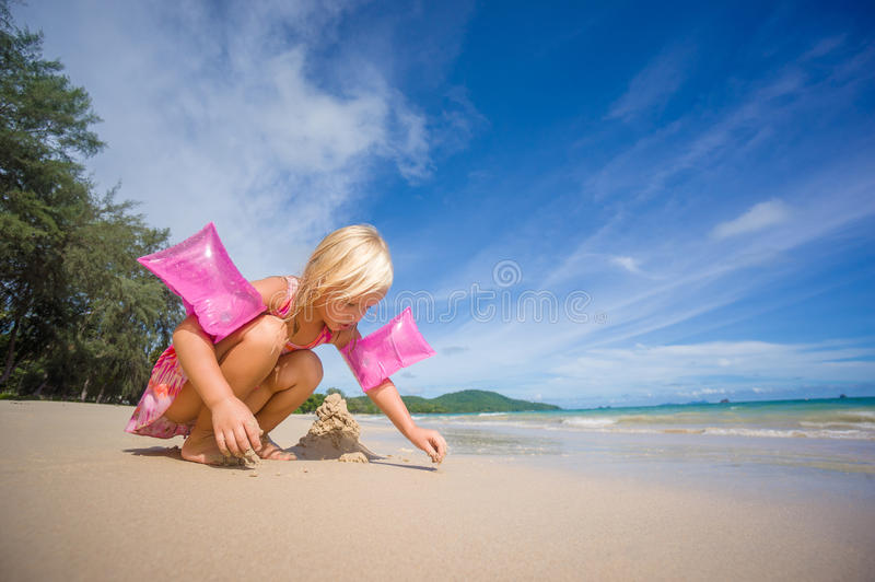 Adorable girl in pink swimming suit and inflatable arm bands build sand tower on ocean beach stock photos