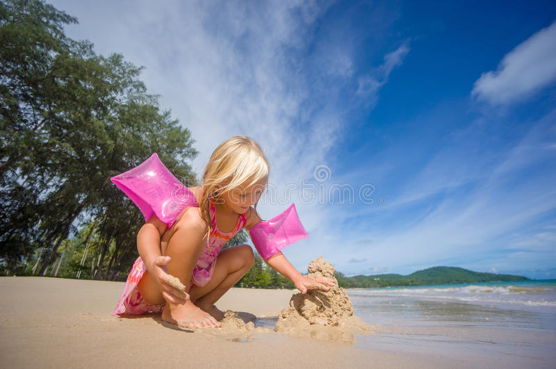 Adorable girl in pink swimming suit and inflatable arm bands build sand tower on ocean beach stock images