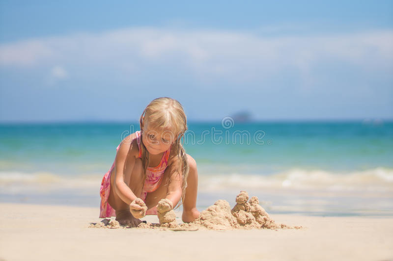 Adorable girl in pink swimming suit play on beach making sand to royalty free stock images