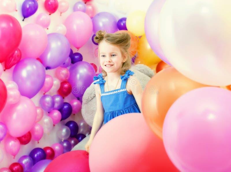 Adorable girl posing among colorful balloons stock photo