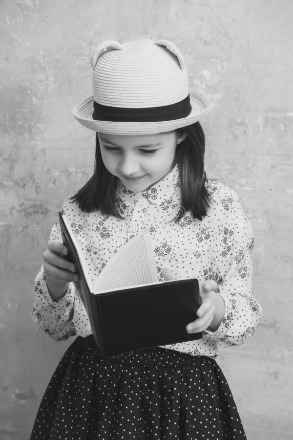 Adorable girl reading black note book stock photography