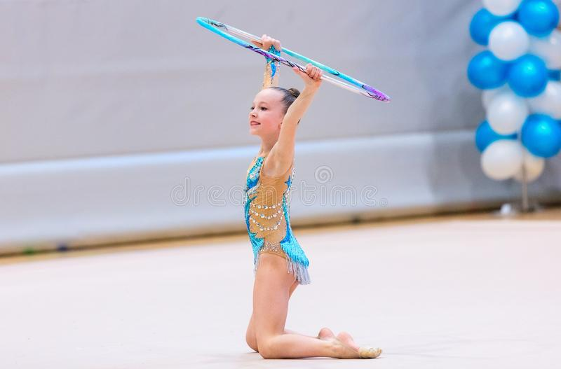 Adorable girl competing in rhythmic gymnastics. Adorable girl in rhythmic gymnastics competition with hoop royalty free stock photo