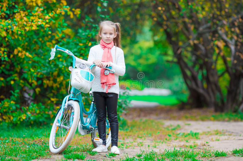 Adorable girl riding a bike at beautiful autumn day outdoors stock image
