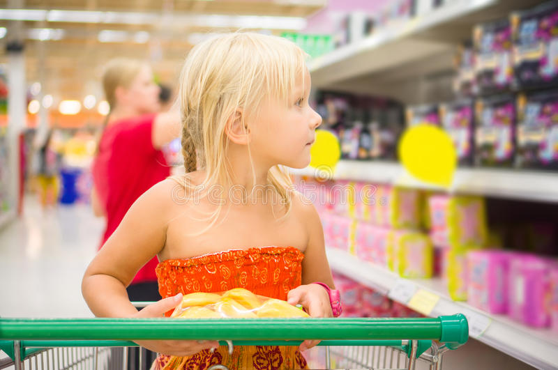 Adorable girl in shopping cart looks at goods on shelves in supermarket stock photography
