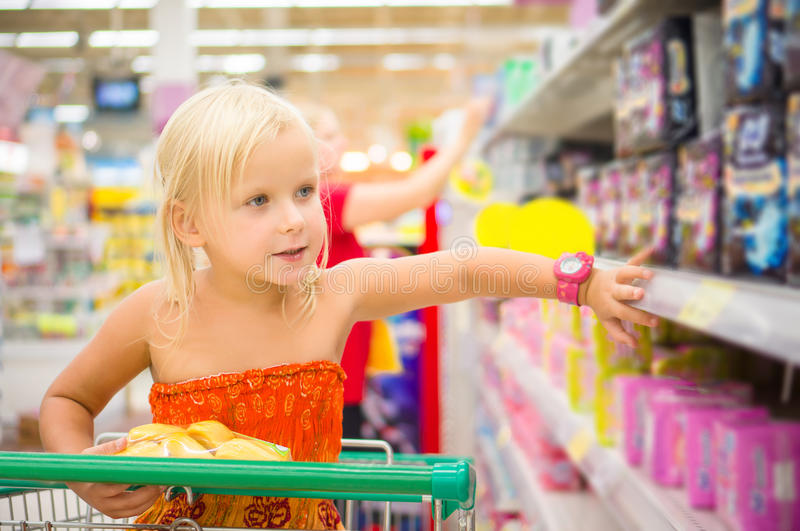 Adorable girl in shopping cart looks at goods on shelves in supermarket royalty free stock image