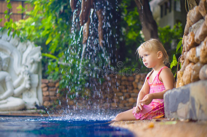 Adorable girl sit on pool side with small waterfall on back stock image