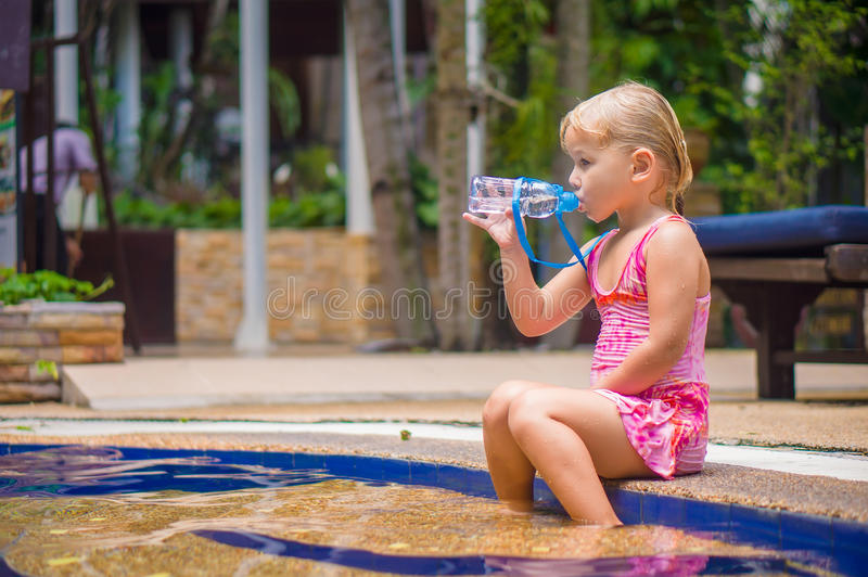 Adorable girl sit in pool on stairs stock photos