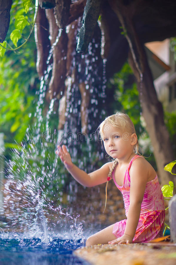 Adorable girl sit and splashing on pool side with small waterfall on back stock photo