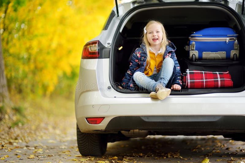 Adorable girl sitting ain a car trunk ready to go on vacations with her parents. Child looking forward for a road trip or travel. Autumn break at school royalty free stock photos