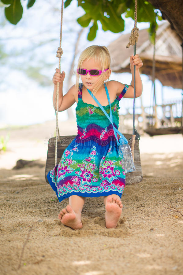 Adorable girl in sunglasses sit on rope swing under palm trees o royalty free stock photos