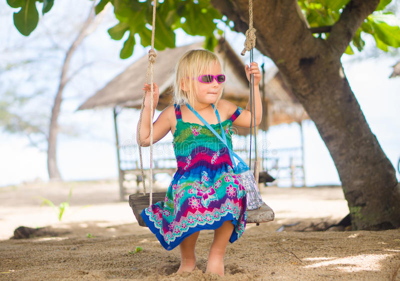 Adorable girl in sunglasses sit on rope swing under palm trees o royalty free stock image
