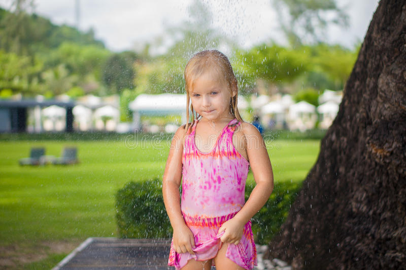 Adorable girl take shower under tree at tropical beach resort royalty free stock photos