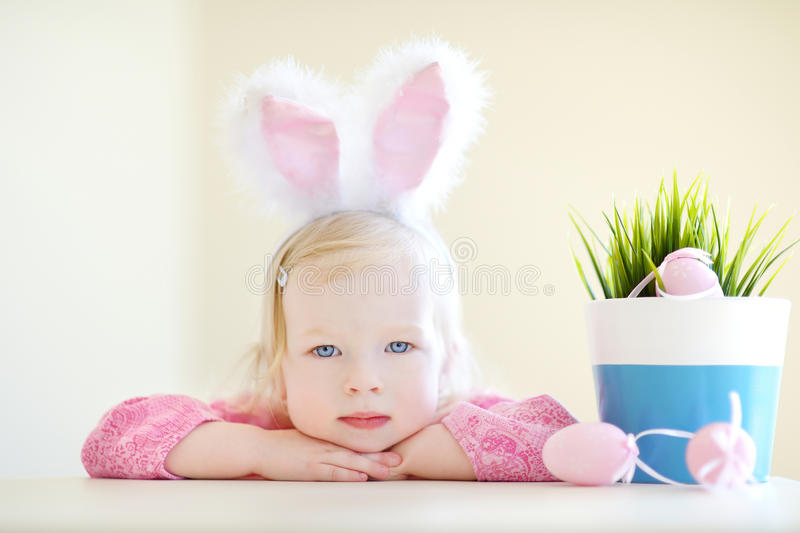 Adorable girl wearing bunny ears on Easter. Adorable toddler girl wearing bunny ears playing with colorful Easter eggs royalty free stock photos