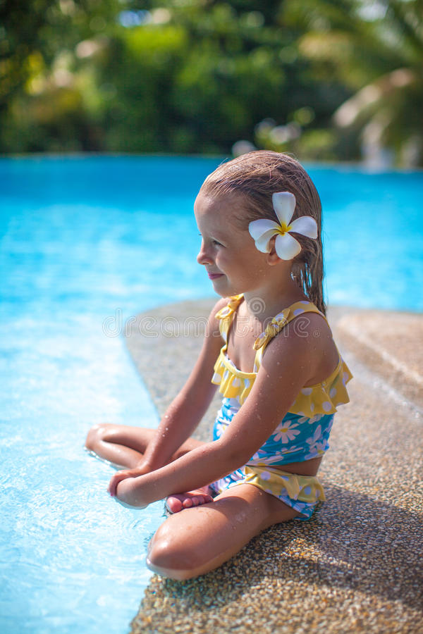 Free Adorable Girl With Flower Behind Her Ear Sits Near Stock Image - 32187971