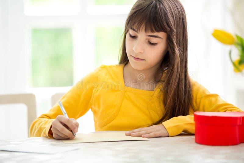 Adorable girl writing greeting card stock photography