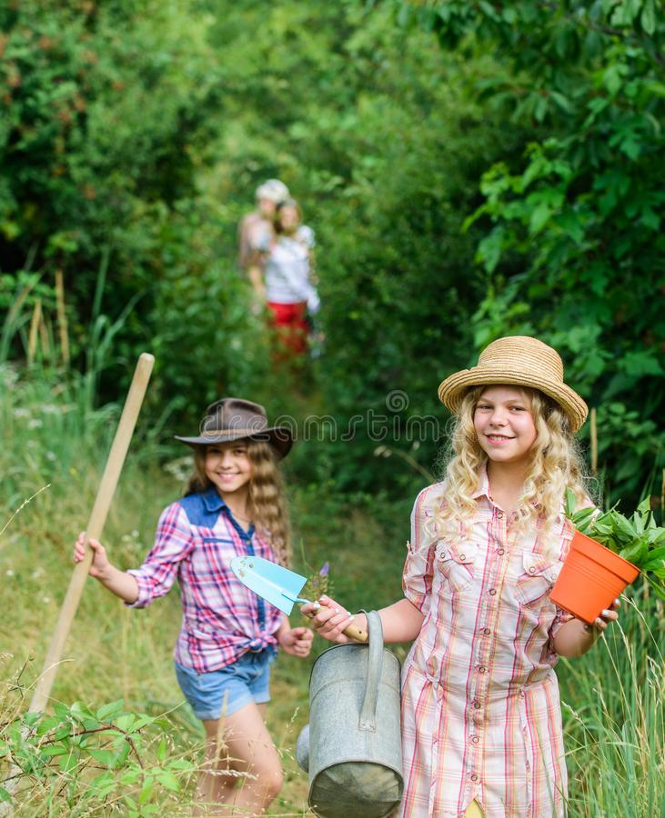Adorable girls in hats going planting plants. Kids siblings having fun at farm. On way to family farm. Taking care of royalty free stock photos