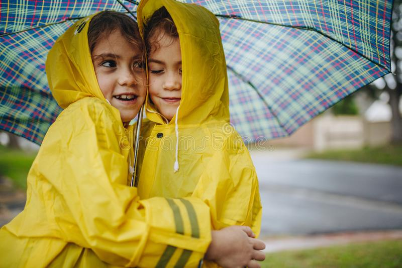 Adorable girls in raincoats hugging each other under umbrella royalty free stock photography