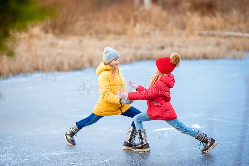 Adorable girls skating on ice rink outdoors in winter snow day. Adorable little girls skating on ice rink outdoors in winter snow day stock photos