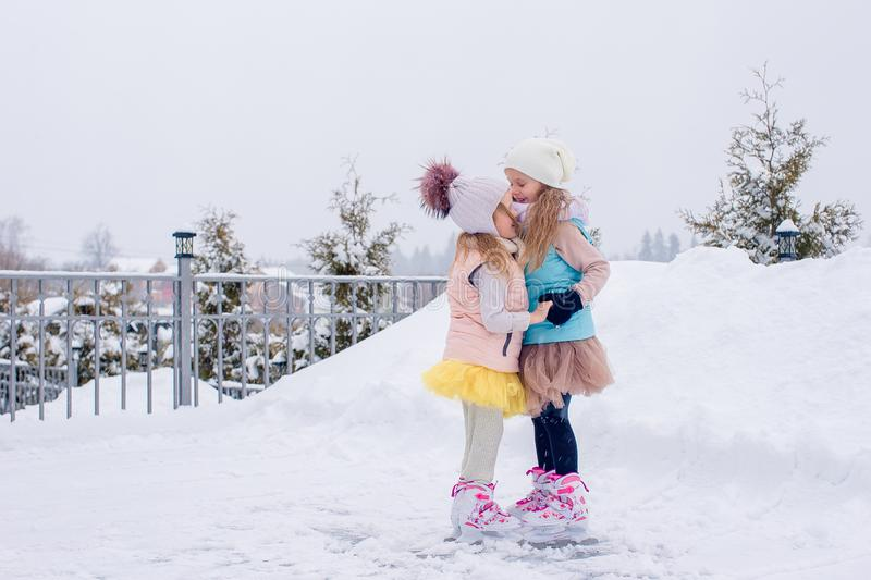 Adorable girls skating on ice rink outdoors in winter snow day. Adorable little girls skating on ice rink outdoors in winter snow day stock photo
