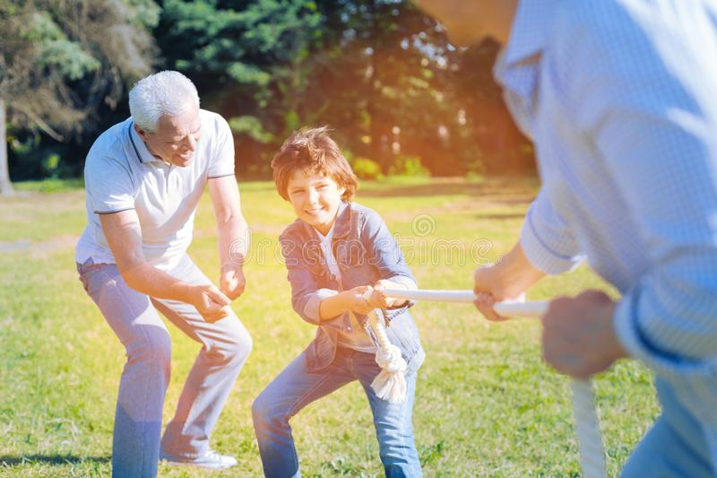 Adorable grandfather cheering for grandson competing with father. Cmon you can do it. Thoughtful senior men getting excited while encouraging his little grandson stock image