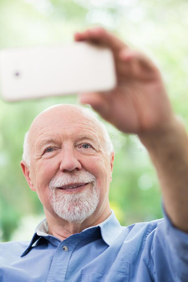 Grandfather taking selfie with his mobile phone royalty free stock photos