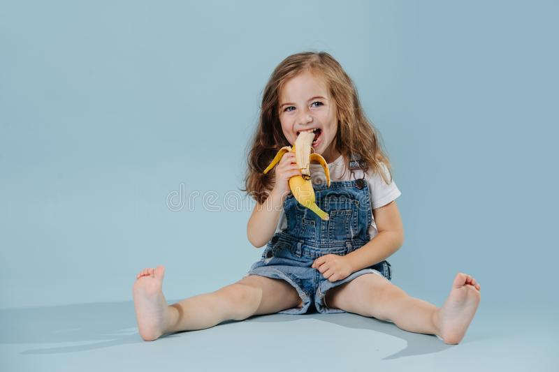 Little girl is eating banana, while sitting on the floor over blue background royalty free stock photo