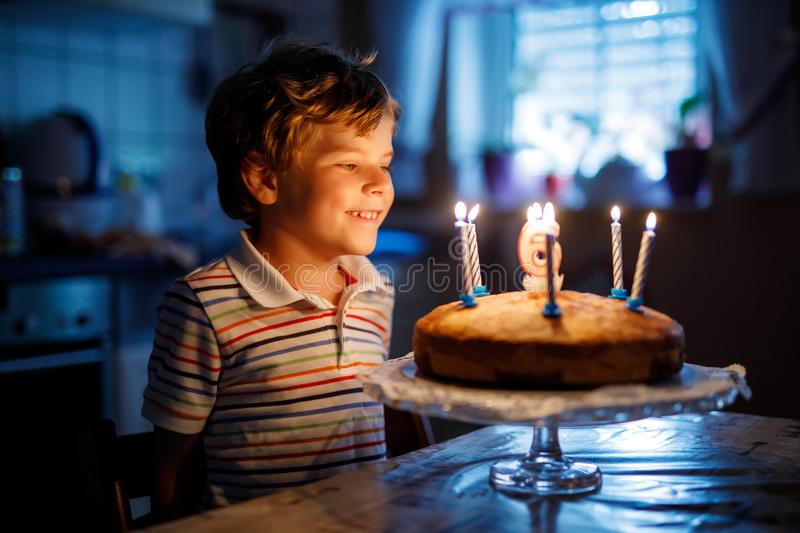 Adorable happy blond little kid boy celebrating his birthday. Child blowing candles on homemade baked cake, indoor. Birthday party for school children, family royalty free stock photos