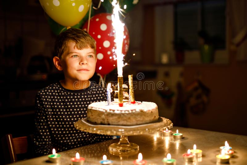 Adorable happy blond little kid boy celebrating his birthday. Child blowingcandles on homemade baked cake, indoor. Adorable happy blond little kid boy royalty free stock images