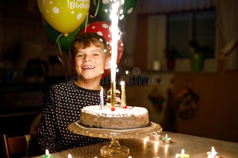 Adorable happy blond little kid boy celebrating his birthday. Child blowingcandles on homemade baked cake, indoor. Adorable happy blond little kid boy royalty free stock image