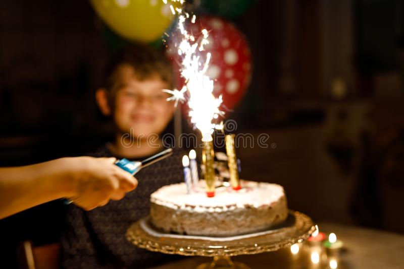 Adorable happy blond little kid boy celebrating his birthday. Child blowing candles on homemade baked cake, indoor. Birthday party for school children stock images