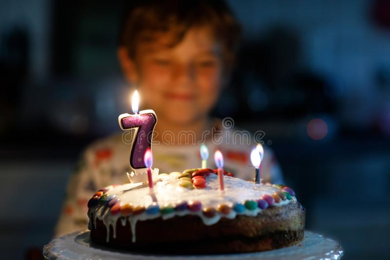 Adorable happy blond little kid boy celebrating his 7 birthday. stock photography