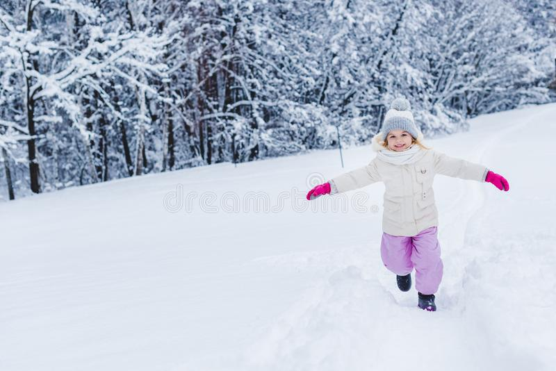 adorable happy child with open arms in mittens running in snow and smiling at camera in winter park royalty free stock photo