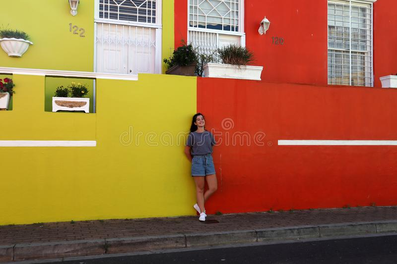 A adorable happy girl take a photo against the colorful wall, in Bo Kaap Quarter street, Cape Town. A Afrikander girl outdoors against red and yellow colorful royalty free stock images