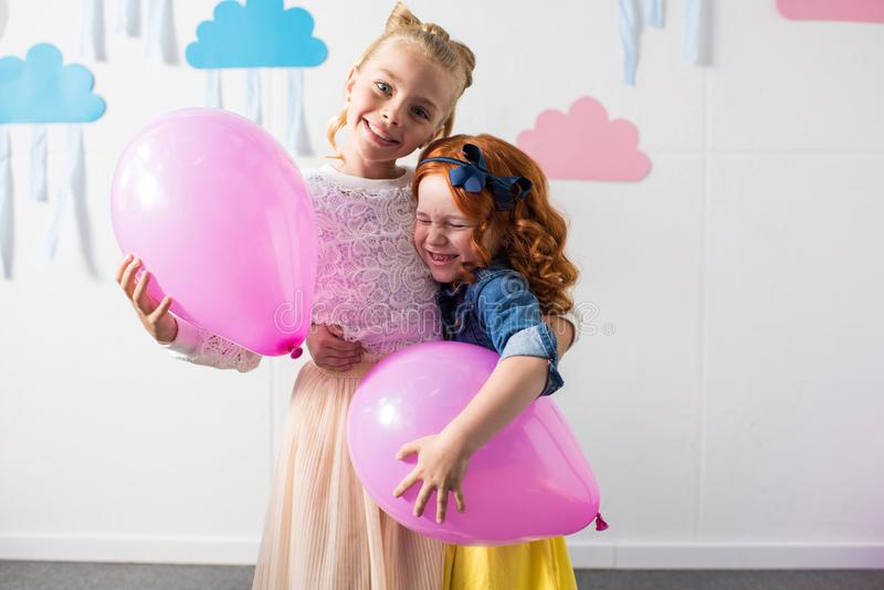 adorable happy girls holding balloons while standing together stock images