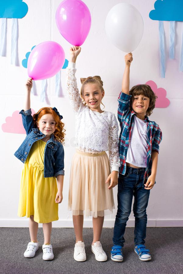 Adorable happy kids holding balloons and smiling at camera at birthday. Party royalty free stock image