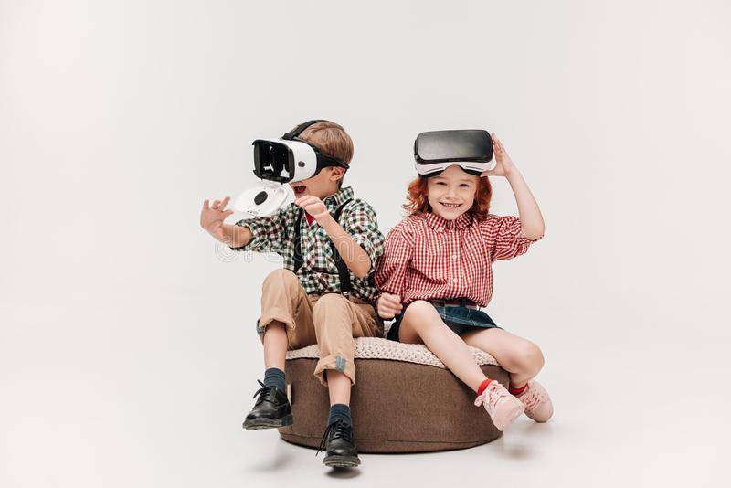 Adorable happy kids using virtual reality headsets. Isolated on grey royalty free stock photos