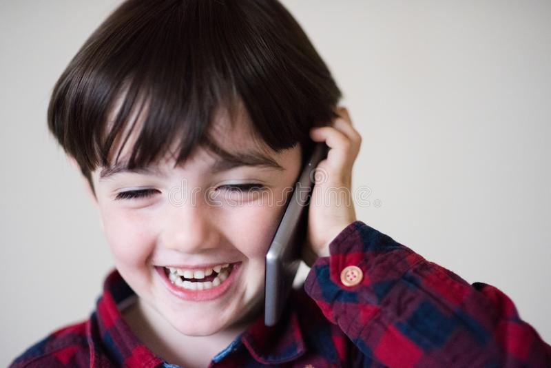 Adorable happy laughing little caucasian boy in plaid shirt talking by cell phone royalty free stock photography